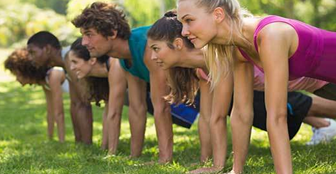 Group of younger adults lined up doing push-ups