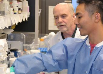 Dr. O'Shea (left) watches as NIAMS visiting fellow Kigoshi Hirahara M.D. Ph.D. works in the lab of the NIAMS Molecular Immunology and Inflammation Branch.